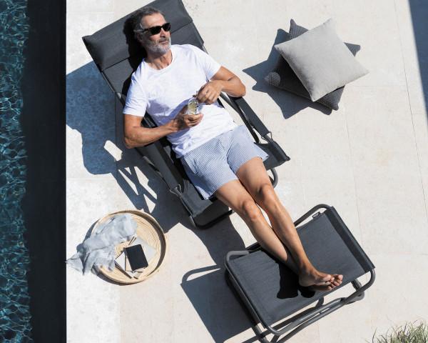 Lafuma Liegestuhl Transabed Privileg in der Gestellfarbe Titane und eine Batyline® Hedona Bezug in der Farbe Onyx Mann am m Pool - bowi.ch