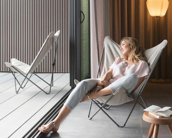 Lafuma Liegestuhl Sphinx Privileg in der Gestellfarbe Titane mit Batyline® Hedona Bezug Latte auf einem Holzboden mit Frau - bowi.ch