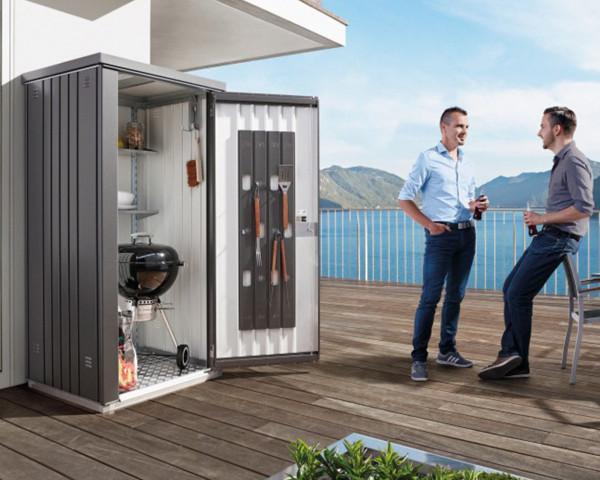 Stimmungsbild von Biohort Geräteschrank in der Farbe Quarzgrau-metallic im Garten mit geöffnetem Türen - bowi.ch