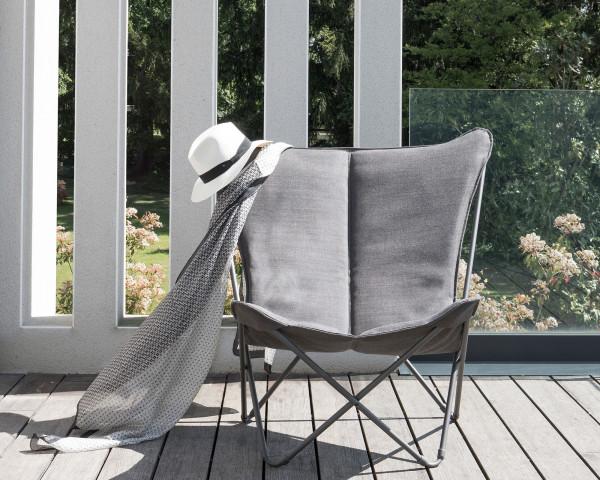 Lafuma Liegestuhl Sphinx Privileg in der Gestellfarbe Titane mit Batyline® Hedona Bezug Onyx auf einem Holzboden mit Kuscheldecke und Hut - bowi.ch